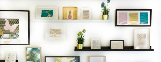biela stena s poličkami, obrazmi, kvetináčmi a doplnkami
