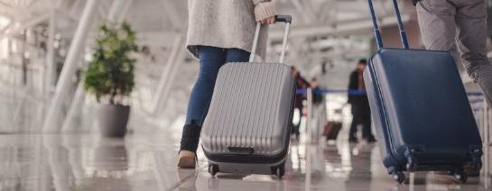 Cestujúci na letisku ťahajú šedý škrupinový kufor na kolieskach a modrý škrupinový kufor na kolieskach